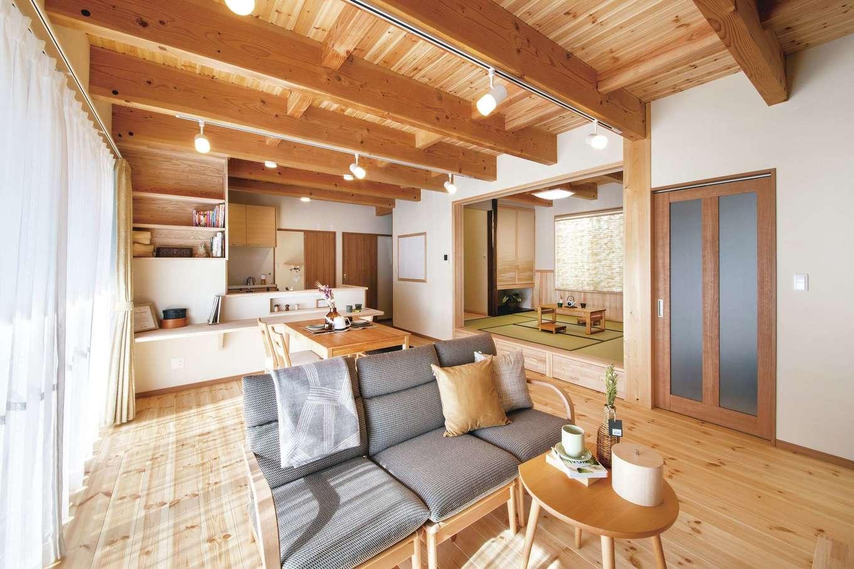 住まいるコーポレーション【デザイン住宅、自然素材、間取り】パインの無垢の床と珪藻土の壁で仕上げたナチュラルテイストのLDK。小上りの和室がリビングと繋がり、どこにいてもお互いの気配を感じられる。ダイニング、リビング、小上がりと、座ってくつろげるスペースがいろいろあるので、友だちや仕事仲間を大勢招いてホームパーティも楽しめそう!