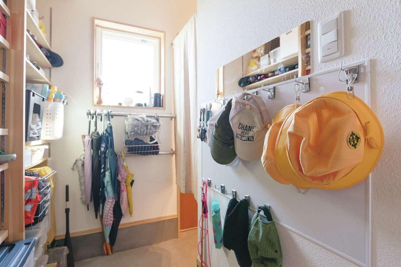 Casa(カーサ)【子育て、間取り、平屋】玄関の壁には巨大なホワイトボードを取り付け、マグネットフックで帽子類をずらり整頓。傘用ラックもAさん自ら設置し、帰宅時に子どもたちが自分で片付けられるようにしている