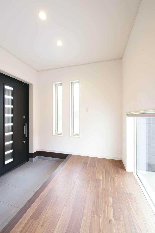 朝日住宅【デザイン住宅、高級住宅、インテリア】玄関の主役は、ホール全体を明るく演出するFIX窓。外には小さな庭が作られ、帰宅した家族をあたたかく迎えてくれる