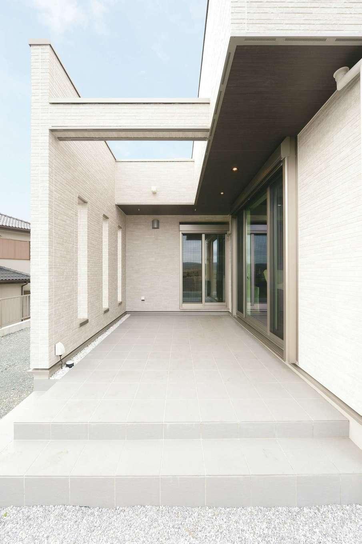 朝日住宅【デザイン住宅、高級住宅、インテリア】テラスを覆うように壁が作られ、近隣住宅からの視線を上手に遮ってくれる。壁際の玉砂利が味わいを演出し、夕暮れ以降は間接照明がロマンティック