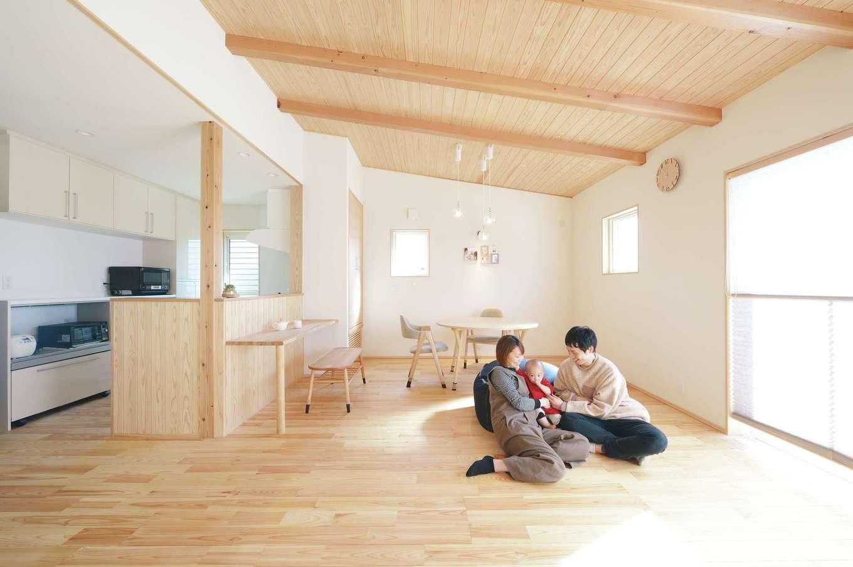 新栄住宅【和風、自然素材、省エネ】「あずみの松」の無垢の温もりが心地よいLDK。勾配天井が開放感をいっそうもたらしてくれる。室内には床下エアコンを採用し、夏は涼しく、冬は暖かい。ソファを置かず広々としたフロアで、家族がくっついてゴロゴロくつろぐのが日課