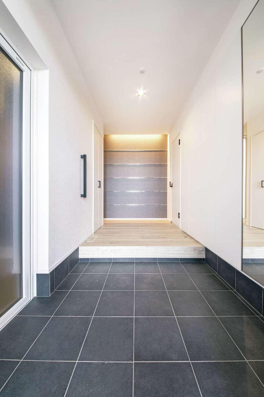 コットンハウス【子育て、平屋、ガレージ】白×黒×グレーでまとめた玄関。左手の入り口はビルトインガレージに続いている。正面のグレーの壁にはスチールのラインを入れてクールに演出