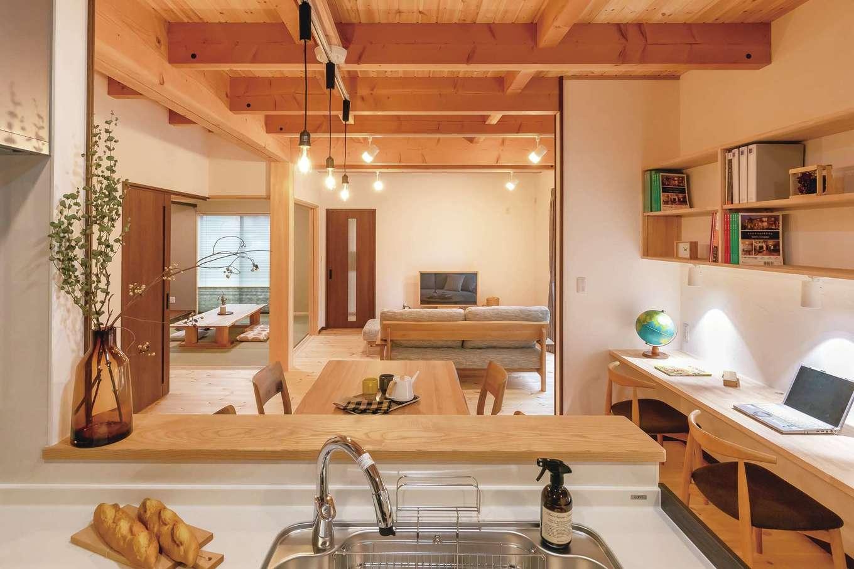 住まいるコーポレーション【デザイン住宅、自然素材、間取り】対面式キッチンの正面にダイニングテーブルを配置したことによって、キッチンから一直線にダイニングとリビングを眺めることができる