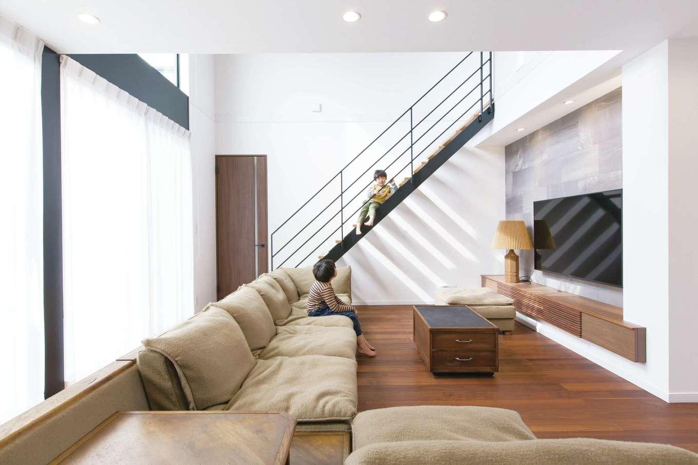 デザインハウス【デザイン住宅、子育て、高級住宅】アイアンのストリップ階段が、壁に美しい影を描く。テレビの背面壁には石目調のエコカラットを使い、上質感をプラス