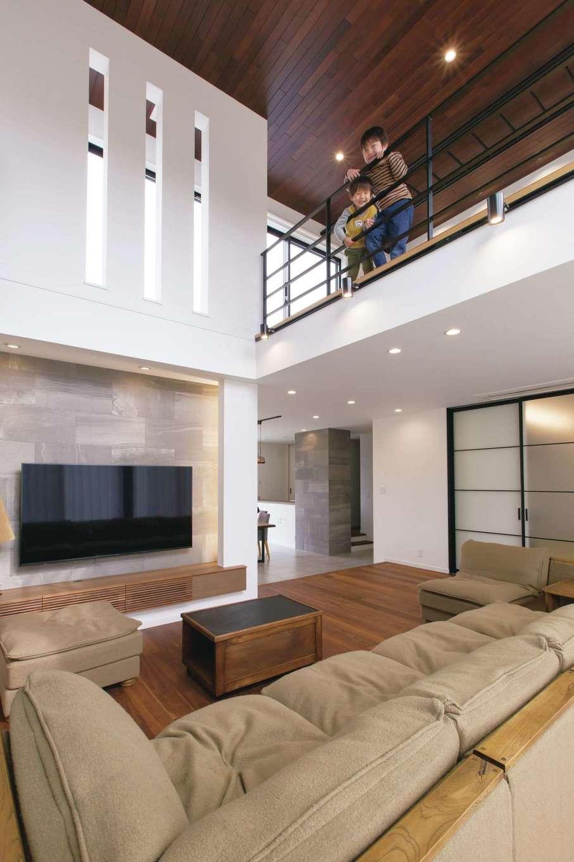 デザインハウス【デザイン住宅、子育て、高級住宅】南北両側から光が降り注ぐ明るい吹き抜けと2階ファミリールームが繋がり、1階で過ごしていても、子どもたちの遊ぶ気配を感じることができる。視線をさえぎる扉がなく、開放感も抜群。大きな一室空間だが断熱性能に優れ、寒さを感じることは少ないそう。憧れだった大阪のTRUCKのソファに座って、のんびりくつろぐのが贅沢なひととき