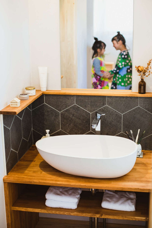 KANAZAWA STYLE/金澤建築【収納力、自然素材、平屋】デザインと使い勝手を両立した造作の洗面台。水はね防止のタイル、かわいいフォルムのボウル、鏡の形状、収納など、ディテールにまでとことんこだわり、熟練大工の技でていねいに仕上げた