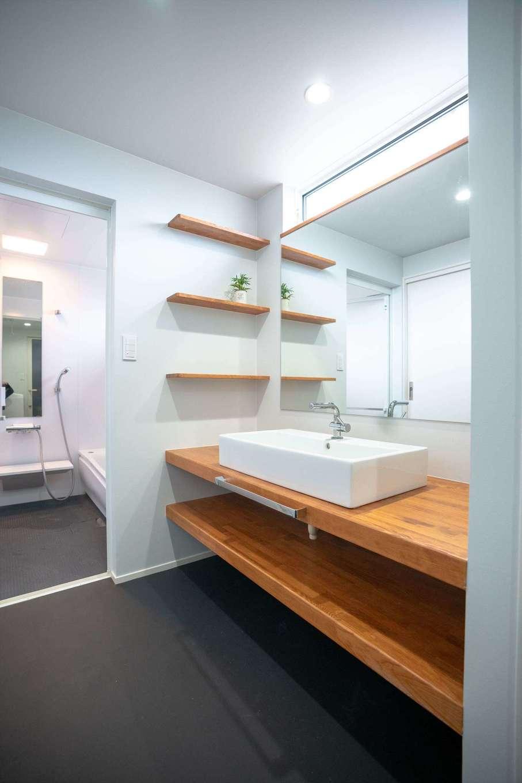 山脇木材【趣味、省エネ、建築家】白と黒を基調とした水回り空間に木の温かみを添えた、造作の洗面スペース。鏡もシンクも大きめにし、シンプルかつ機能的にデザイン