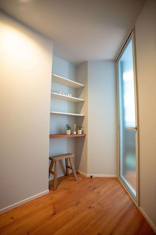 山脇木材【趣味、省エネ、建築家】玄関からリビングに入る手前に設けた飾り棚には、奥さまのお気に入りの小物やグリーンを飾って。リビングのドアは半透明にして玄関ホールに明るさを確保