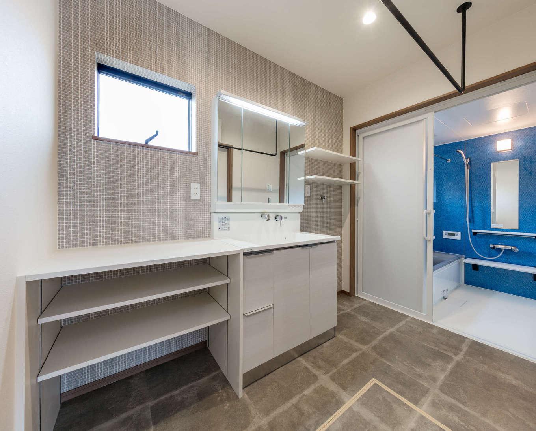 山脇木材【デザイン住宅、子育て、収納力】フロアタイルと壁をグレーで統一したシンプルモダンな洗面スペースに、浴室のブルーの壁がよく映える。室内干しのポールもデザイン性にこだわり、アイアン製を採用