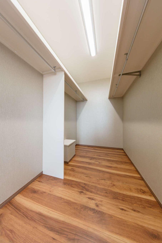山脇木材【デザイン住宅、子育て、収納力】寝室のウォークインクローゼットは広さが4畳。壁の両側にハンガーパイプを設け、夫妻の衣類を分けて収納。衣類を選びやすく、使い勝手が抜群