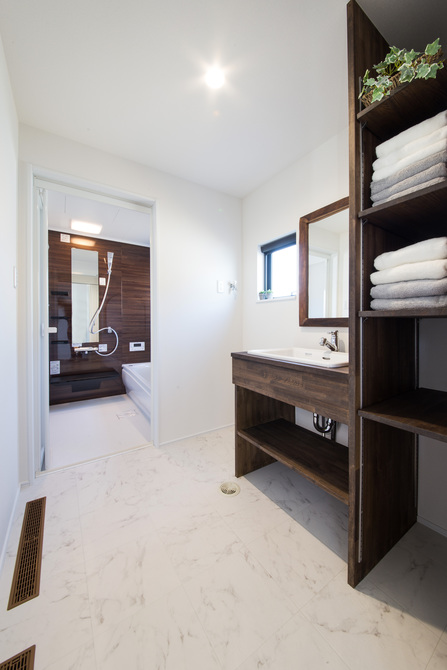 小幡建設【デザイン住宅、子育て、間取り】洗面の造作も他の部屋の色合いに合わせた。床にあるのは「1Alls systemu」の通気口。寒くなりがちな脱衣室も他の部屋と室温が同じ