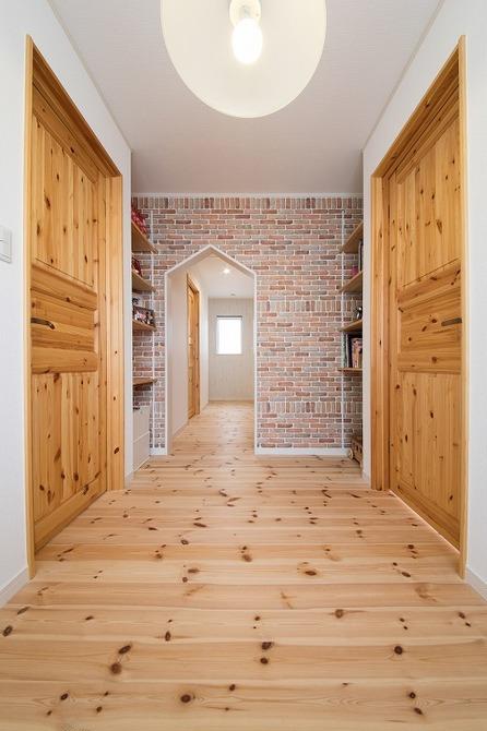 小幡建設【デザイン住宅、子育て、収納力】2階のフリースペース。扉にも木材を使い空間を統一。レンガ調のクロスがアクセントになっている