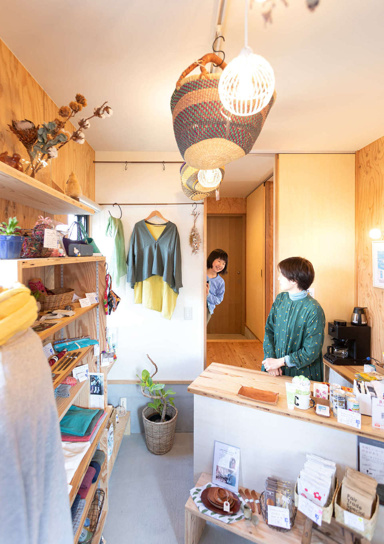 入政建築【デザイン住宅、子育て、間取り】こじんまりとした店内には、フェアトレードのコーヒーや食品などが並ぶ。店内の壁も構造用合板で仕上げてあるので、好きな場所にフックや棚を設けてディスプレイできる。会計カウンターの背後に住居への出入口があり、お子さまがママの様子をのぞきにくることも