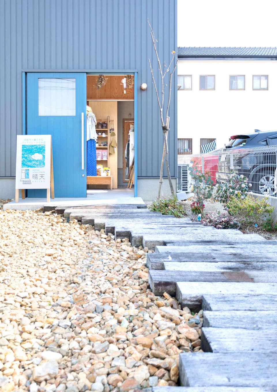 入政建築【デザイン住宅、子育て、間取り】ブルーのドアが印象的な、フェアトレード雑貨店「晴天」のエントランス。家族用の玄関ポーチは店舗用の玄関と向きを変えて外壁で隠し、プライバシーを確保した