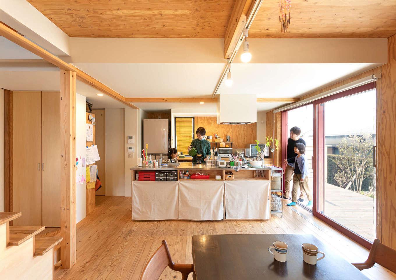 入政建築【デザイン住宅、子育て、間取り】スギの床の柔らかな感触と構造用合板の飾り気のない雰囲気が心地よいLDK。アイランドキッチンに立つと、室内や庭を一望できる。ステンレストップのアイランドキッチンは『入政建築』の造作によるもの。キッチンの横には収納スペースも確保