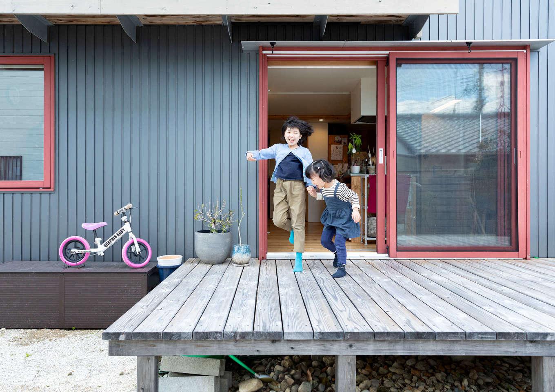 入政建築【デザイン住宅、子育て、間取り】アイランドキッチンの横に広いウッドデッキを設置。北面に玄関を設けたことで、南面の庭はプライベート感にあふれ、周囲を気にせず家族でのびのびくつろげる。晴れた日の休日には、ご主人が植えた庭の樹々をながめながら青空ブランチをするのが楽しみ