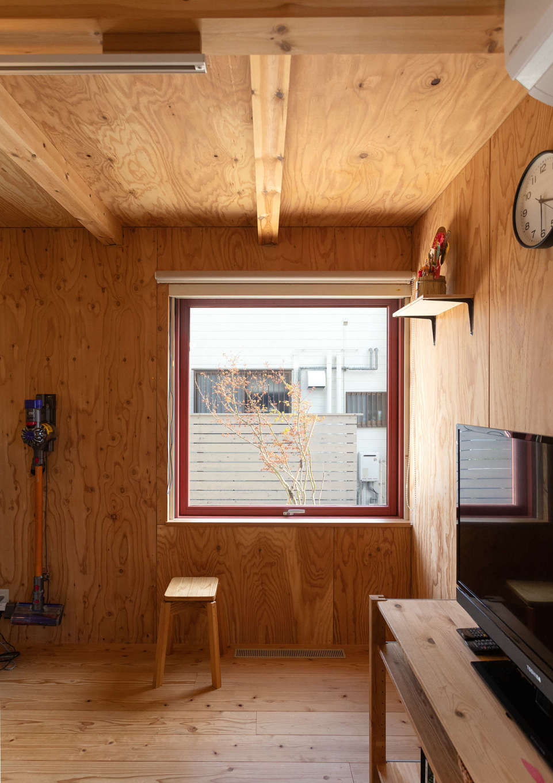 入政建築【デザイン住宅、子育て、間取り】1階の開口部には赤い木製サッシを採用。断熱性も高く、意匠性にもすぐれているため、インテリア・アクセントとして木の空間を引き立てている。室内から庭の四季も楽しめる