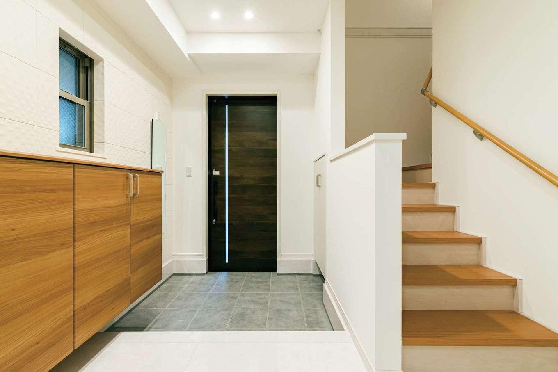 玄関の壁に用いたエコカラットは立体感のある個性的なデザイン。上げ天井で縦空間にもアクセントを