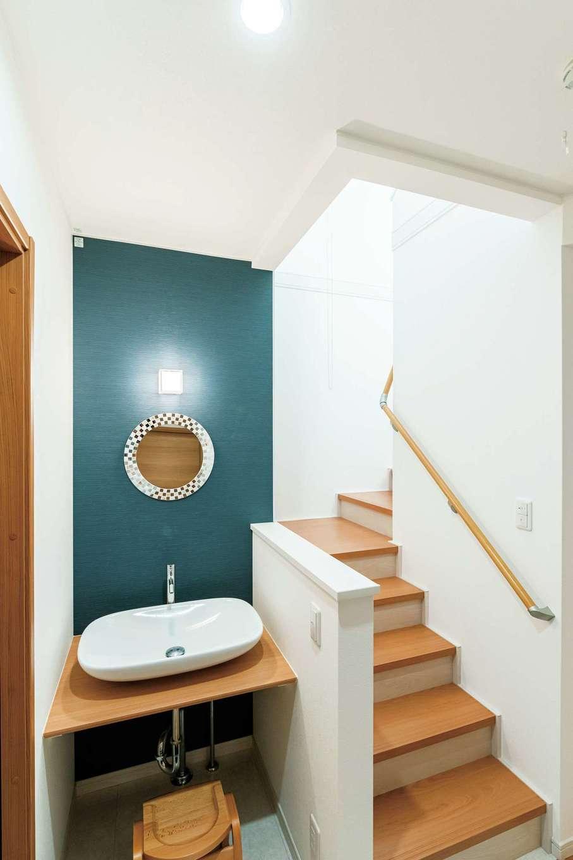 階段をのぼり2階に上がった先に、丸い鏡がかわいい手洗いを配置