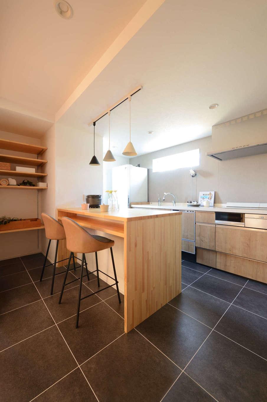 野本建築【趣味、自然素材、ペット】壁付けのI型キッチンの対面にダイニングカウンターを設けて省スペースを実現。カウンターのキッチン側は収納スペースになっている。ダイニングの奥にも収納棚を確保した