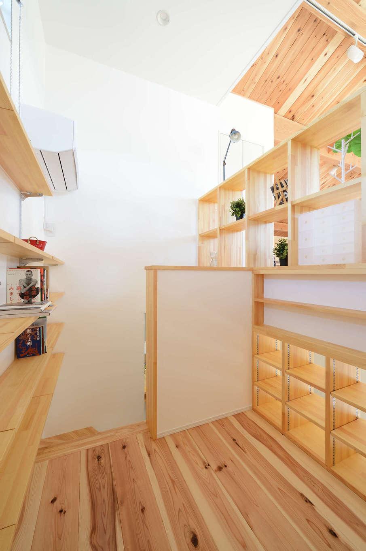 野本建築【趣味、自然素材、ペット】階段の踊り場にあたるスキップフロアには造作の書棚を両側に設け、ミニライブラリーとして利用。猫と一緒に階段にちょこんと座って本を読むひとときが、何とも心地よい