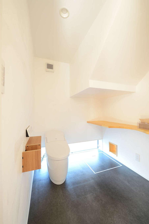 野本建築【趣味、自然素材、ペット】フロアタイルの床と漆喰の壁がオシャレなトイレ。猫用のトイレを置くスペースと、専用の出入口も確保した。出入口の先はスキップフロアの階下にあたり、猫用のスペースとなっている