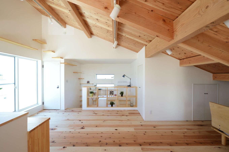 野本建築【趣味、自然素材、ペット】スギのやさしい香りが漂う2階の寝室は、勾配天井が「こもり感」をもたらす心地よい空間。掃き出し窓の先には広いバルコニーもある