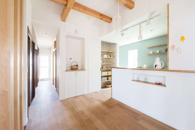 野本建築【子育て、自然素材、インテリア】キッチンの壁はブルーグレーのアクセントクロスを用いて北欧風に演出。パントリーやニッチも、しまうものに合わせて適量適所に設けてある。ダイニング側の白い壁はマグネット仕様にしてあるので、学校のお便りなどを貼っておける