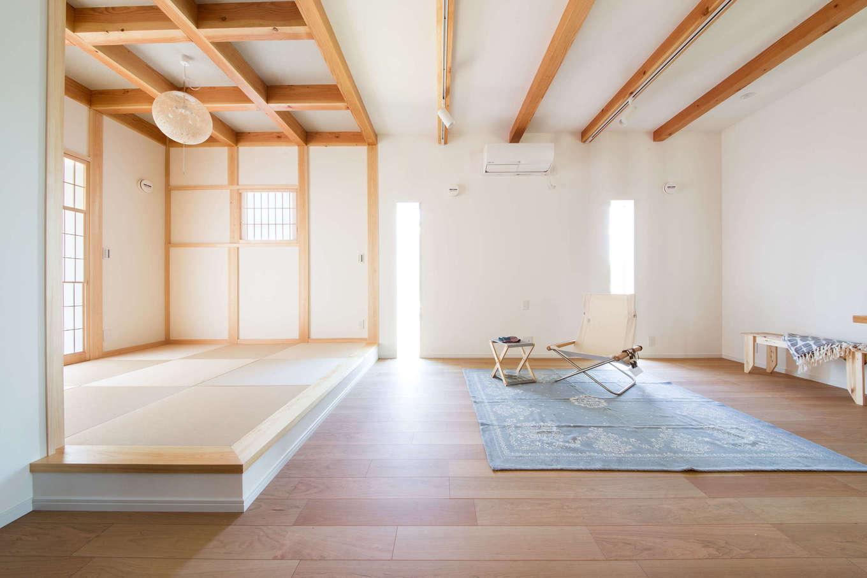 野本建築【子育て、自然素材、インテリア】真壁で格天井の小上がりと、大壁で化粧梁の天井のリビングが対照的に並ぶLDK。どちらも空間にゆとりを持たせてあり、暮らしのシーンに合わせてさまざまなスタイルでくつろげる
