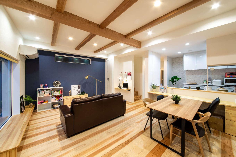 野本建築【子育て、自然素材、インテリア】スギの無垢の床が温かみを感じさせるLDK。木の香りに包まれて、家族一緒に心地よくくつろげる。窓際には長いベンチを設けてあり、来客時には腰掛けとして活躍。リビングの壁面にはパソコンコーナーも設けてある