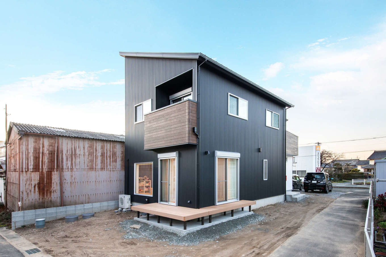野本建築【子育て、自然素材、インテリア】片流れの屋根のシャープなフォルムと黒い外壁がクールな外観。ウッドデッキをL字型に設けて、隣の実家と行き来がしやすいように工夫されている