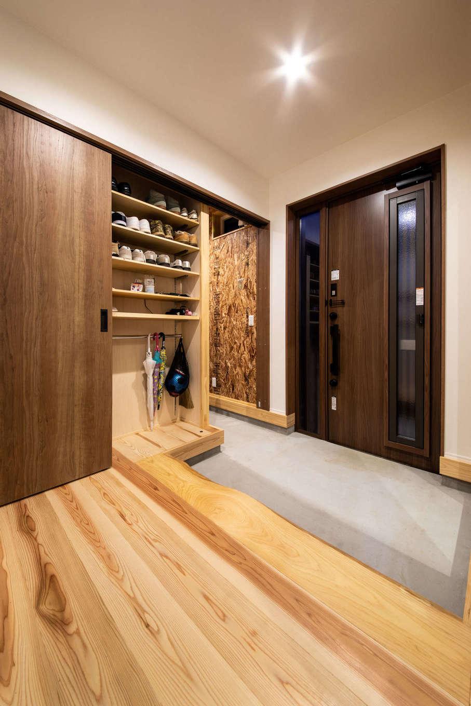 野本建築【子育て、自然素材、インテリア】シューズクローク付きの玄関。シューズクローク内はOSBボードの壁とコンクリートの床で男前にコーディネート。靴や上着のほか、ご主人の趣味のスケボー道具もまとめてすっきり収納できる