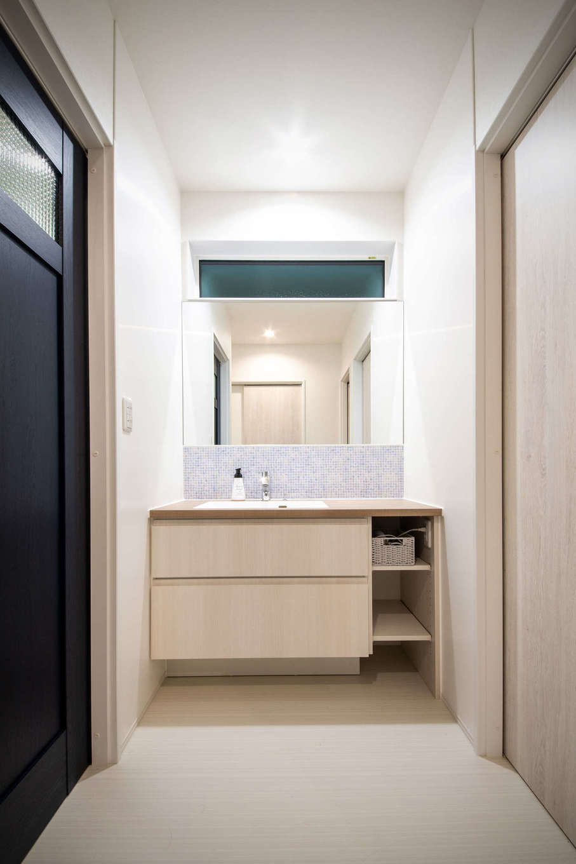 野本建築【子育て、自然素材、インテリア】洗面スペースは脱衣室と仕切って設けてあり、家族が入浴中でも気兼ねなく使えるようにした。洗面台の収納は床面を空けてあるので掃除がしやすく、体重計などもしまいやすい