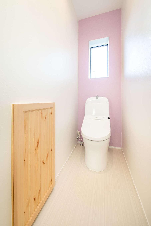 野本建築【子育て、自然素材、インテリア】奥さまがセレクトしたピンクのアクセントクロスが明るくやさしい雰囲気を醸し出すトイレ。木扉の奥は収納スペース