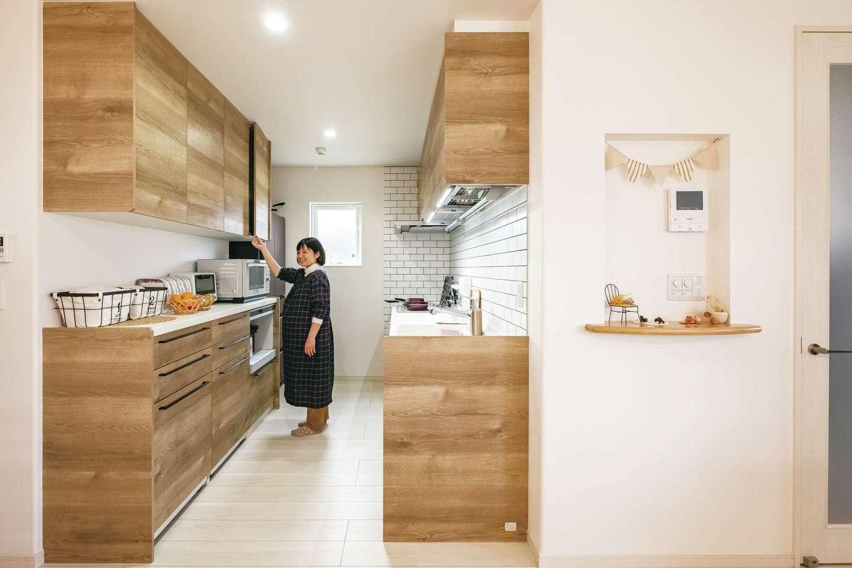 リビングの見せ梁に合わせて選んだ木目調のキッチン。右側の壁は清潔感とデザイン性を兼ね備えた白タイルを張った