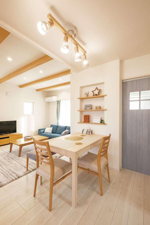 イデキョウホーム【デザイン住宅、省エネ、屋上バルコニー】キッチンを奥にまとめたことで、リビングとキッチンの間にバランスよくダイニングスペースを配置できた。ペールブルーのドアで北欧風のイメージに