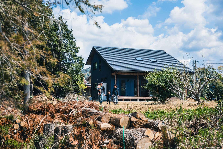 安形【デザイン住宅、子育て、自然素材】おおらかな大屋根の意匠と、黒×茶色の色合いが周囲の風景と調和した外観。「いずれは庭で家庭菜園でもやろうかと思っています」とご主人