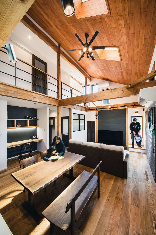 安形【デザイン住宅、子育て、自然素材】吹抜けの勾配天井が圧倒的な開放感をもたらすLDK。2階の廊下のアイアンの手すりや黒いアクセントクロスで、クールで男前な雰囲気を演出。壁面にはスタディコーナーを設けてあり、キッチンから子どもが勉強する様子を見守れる