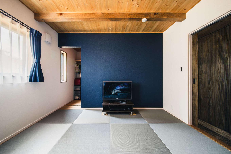 安形【デザイン住宅、子育て、自然素材】キッチンの隣に設けた和室。紺色のアクセントクロスと琉球畳で和モダンにコーディネート。壁の背面にはウォークインクローゼットがある。いずれは夫妻の寝室として利用する予定