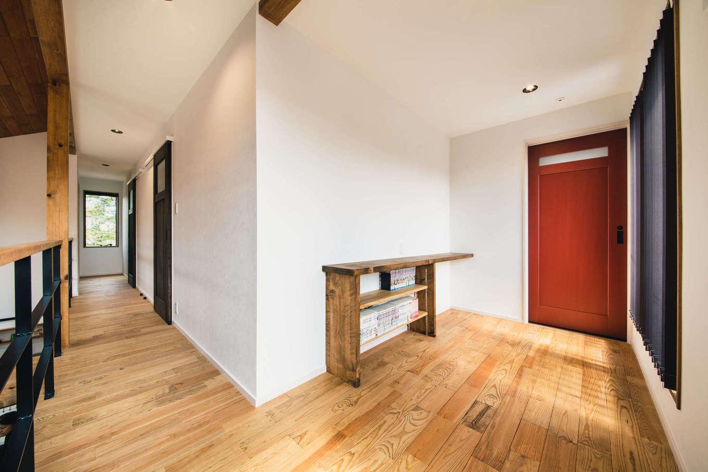 安形【デザイン住宅、子育て、自然素材】階段を上がって正面にあるホールには、造作の書棚カウンターを設置。トイレの赤いドアが空間を引き立てる。ご長女は無垢の床に座り込んで、日向ぼっこをしながら本を読むのがお気に入り。天井には室内干しが備わり、掃出窓の外のバルコニーに外干しもできる