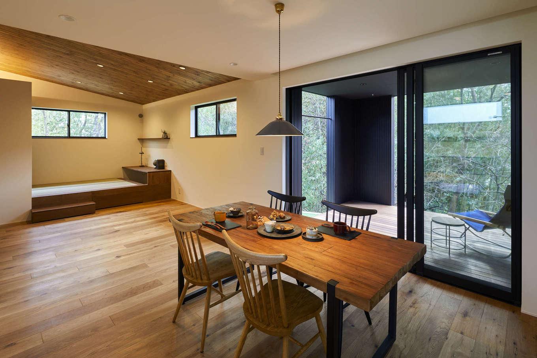 温戸ライフ【デザイン住宅、趣味、自然素材】COOLとモダンが共鳴する大人カッコイイLDK。3方向にグリーンの景色が広がり、どこにいても癒やされる。長く軒を伸ばしたウッドデッキが家の外と中をつなぎ、自然との一体感が心地いい