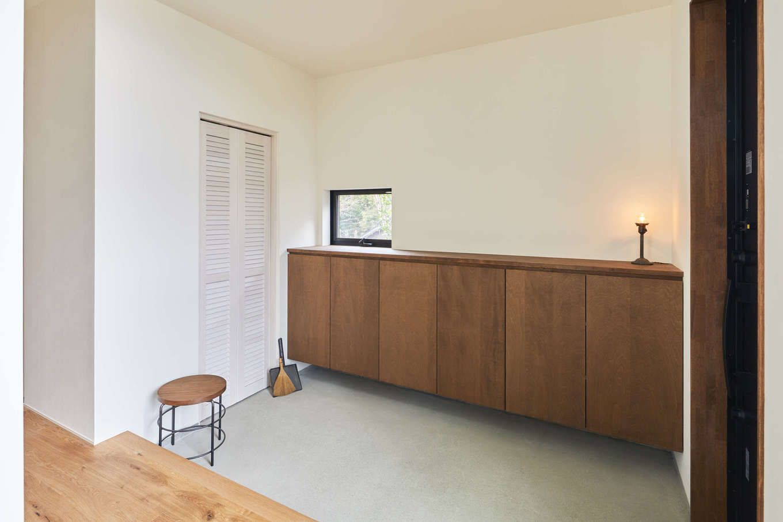 温戸ライフ【デザイン住宅、趣味、自然素材】清潔感あふれるシンプルな玄関ホール。収納も充実し、常にすっきりと見せることができる。壁の角はあえて丸くせず、エッジの効いたシャープな印象に