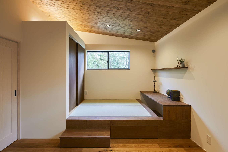 温戸ライフ【デザイン住宅、趣味、自然素材】小上がりの畳コーナーは、子どもを昼寝させたり、洗濯物をたたんだり、お雛さまを飾ったり、多用途に使える。床を40センチ上げたことで圧迫感が出ないよう、勾配天井を採用した。さらに、ウォールナットの天井の自然塗料を拭き取り仕上げにしたことで、床とのメリハリがついた