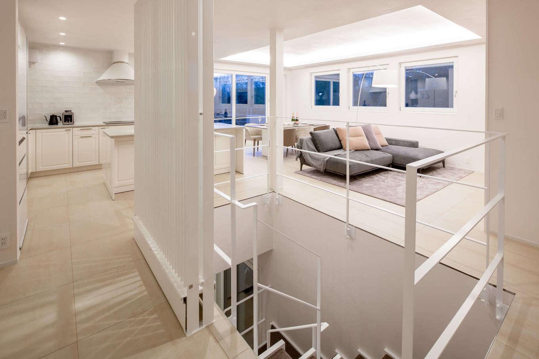 スタイルカーサ【デザイン住宅、趣味、建築家】広々とした2階LDK。部屋全体を白で統一したことで高級感が生まれ、家具や小物で自分たちらしい色を加えた。窓に映る湖の景色は額縁で切り取った写真のように美しい。「光冷暖」の効果で、これだけの大空間でも温度ムラがなく快適に過ごせて、光熱費も抑えられる