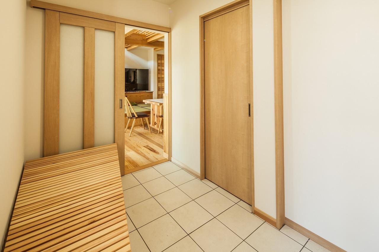 安藤建築【デザイン住宅、自然素材、建築家】玄関ホールは、パントリー、キッチン、リビングへと3方向にアクセスできる動線を確保。造作の腰掛けベンチは家族みんなが重宝している