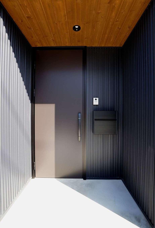 RIKYU (リキュー)【デザイン住宅、間取り、建築家】ガルバリウムの外壁とレッドシダーの軒天がバランス良く調和した玄関ポーチ。深い軒に守られて、雨の日もストレスフリー