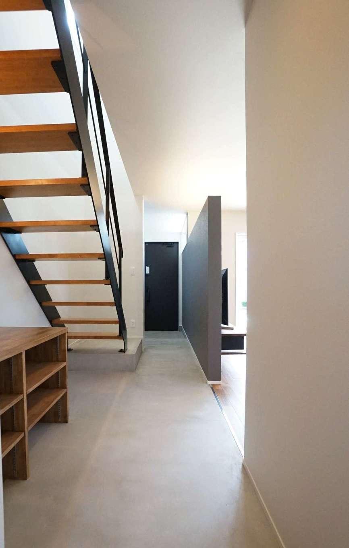 RIKYU (リキュー)【デザイン住宅、間取り、建築家】土間仕上げのスタイリッシュな玄関ホール。LDKとフラットにつなげたことで空間に一体感が生まれ、広く感じられる。さらに、階段をスケルトンにしたことによって視線が抜け、より開放的な雰囲気に。完全に間仕切りしていないので、リビングからの光が届いて明るさも確保