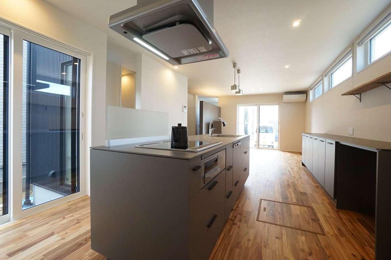 RIKYU (リキュー)【デザイン住宅、間取り、建築家】回遊性の高いアイランドキッチンは奥さまからのリクエスト。シャープなデザインのキッチンは『R+house』オリジナルで、8mmの薄い天板とサイドパネルの美しいフォルムが空間にマッチしている。向かいの窓越しにはシンボルツリーが見える