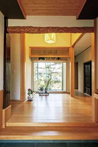 旭建設|高級旅館のような格調高い玄関では、ヒノキの床がゲストを迎える。正面には坪庭も