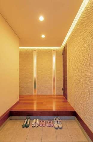 住宅工房 アリアンス|塗り壁と間接照明の温かみに癒やされる玄関ホール。天井まで届くスリットの窓越しに家族の気配を感じるのがポイント